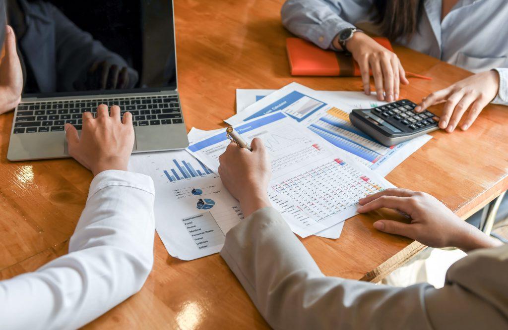 A imagem mostra três pessoas em frente a um notebook. Diversos documentos estão espalhados na mesa, para análise de informações.