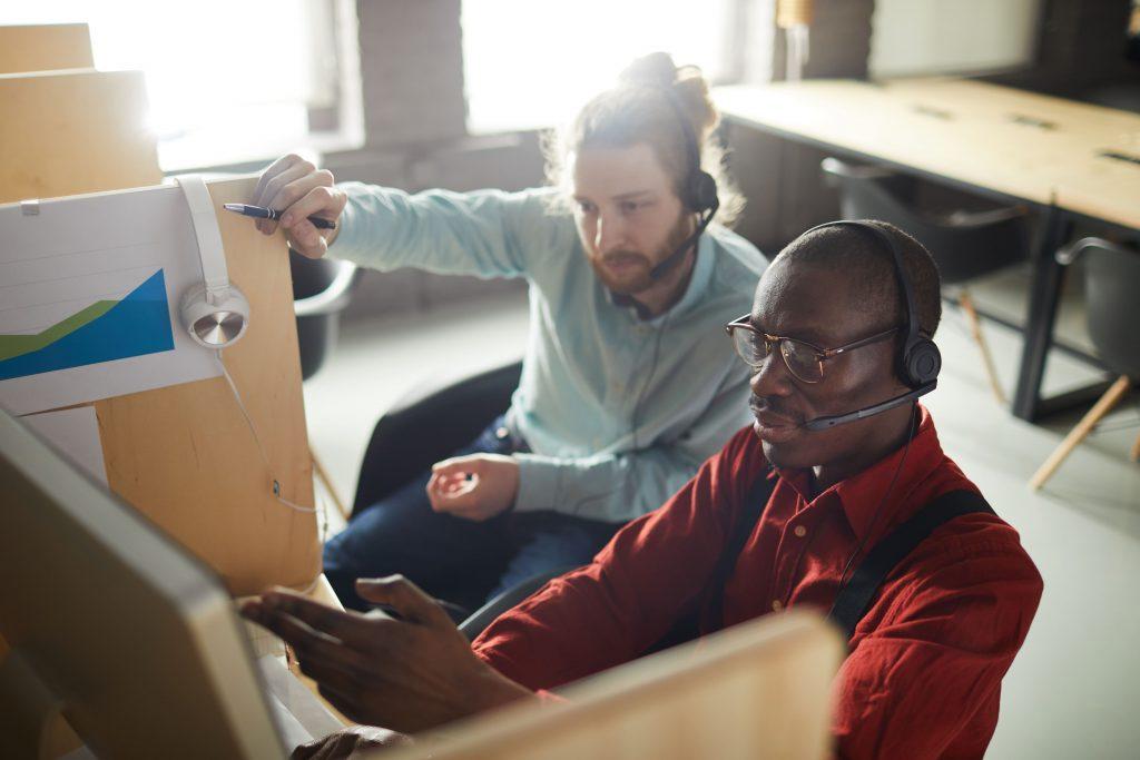 A imagem mostra uma dupla - formada por dois homens -, de operadores de atendimento conversando sobre uma das demandas recebidas.