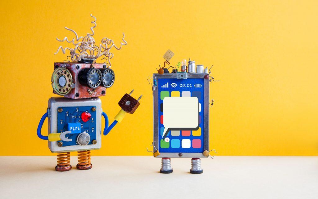 A imagem mostra dois pequenos robôs, uma alusão a ideia de ferramentas de autoatendimento