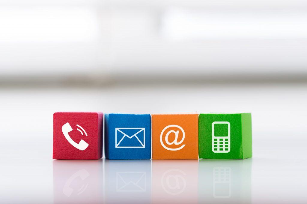 A imagem mostra quadro cubos coloridos alinhados lado a lado. Em cada um deles há a representação de um ícone de comunicação: vermelho: telefone; azul: envelope de carta; laranja: @ ; verde: celular