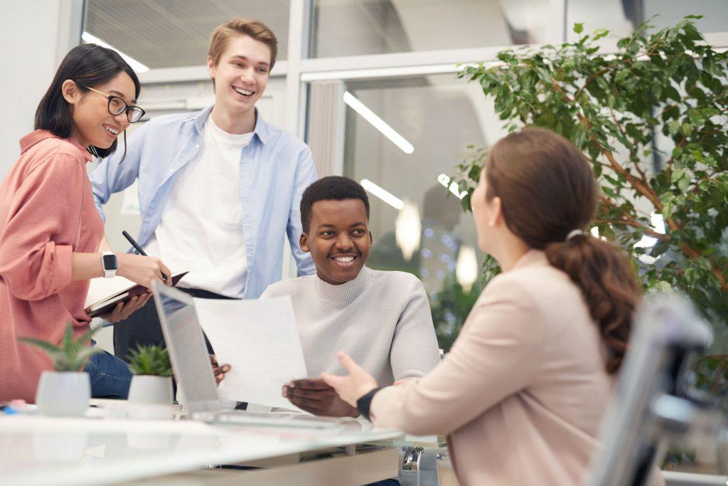 Na imagem temos um grupo de jovens multiétnicos conversando sobre o trabalho.