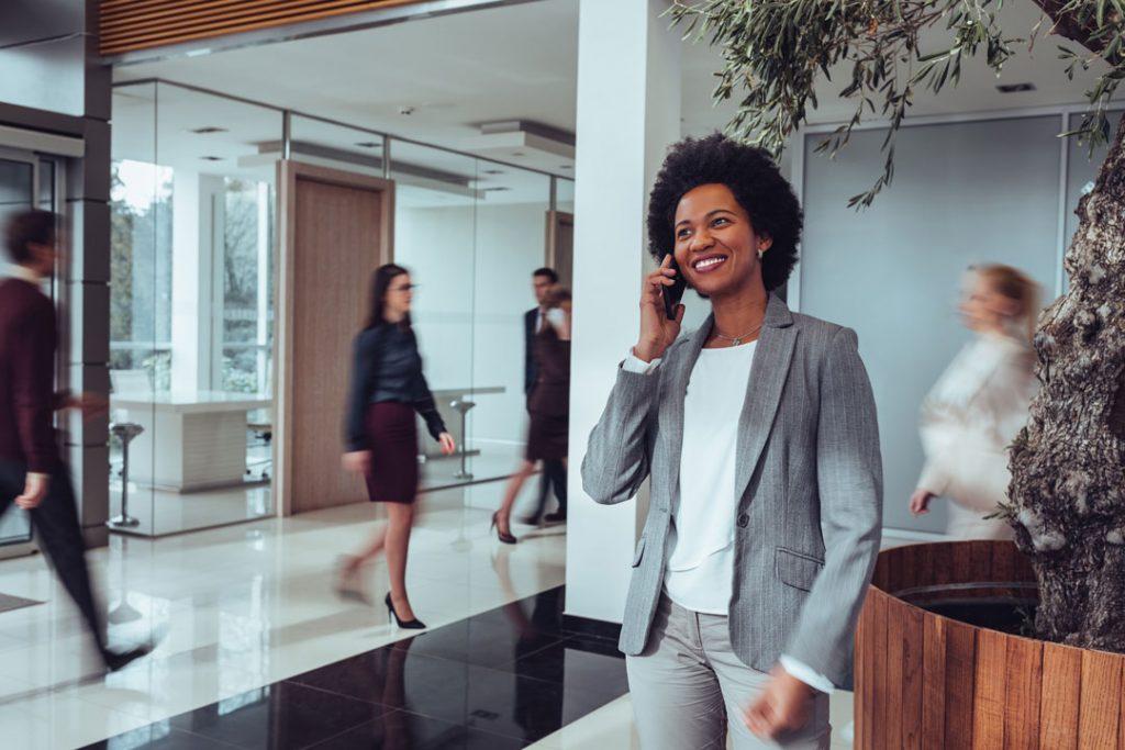 Customer Service: Mulher negra, de roupa social ao telefone sorrindo