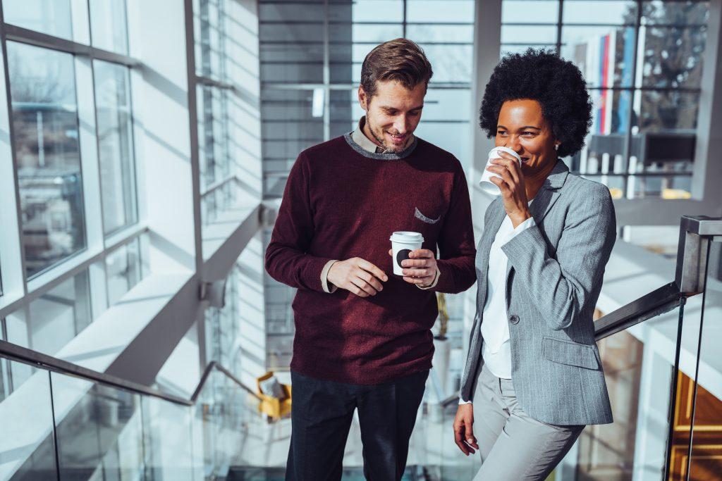 Na imagem temos um homem branco, de cabelo castanho, usando uma roupa social e segurando um café, ao seu lado está uma mulher negra de roupa social, segurando um café. Ambos estão sorrindo.